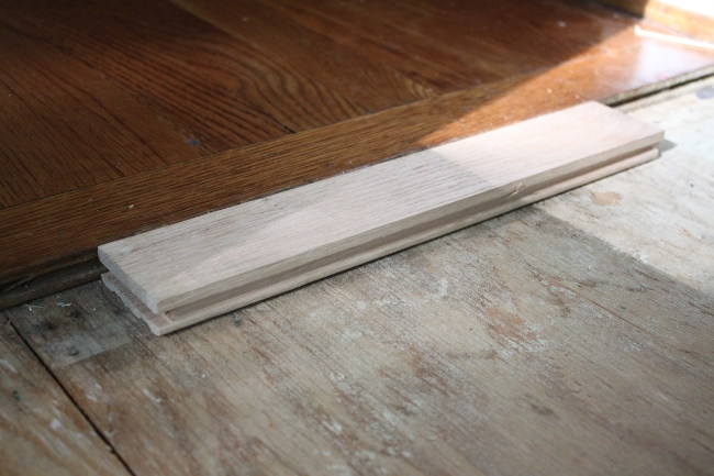 The new unfinished hardwood flooring matched perfectly the height of the existing flooring.