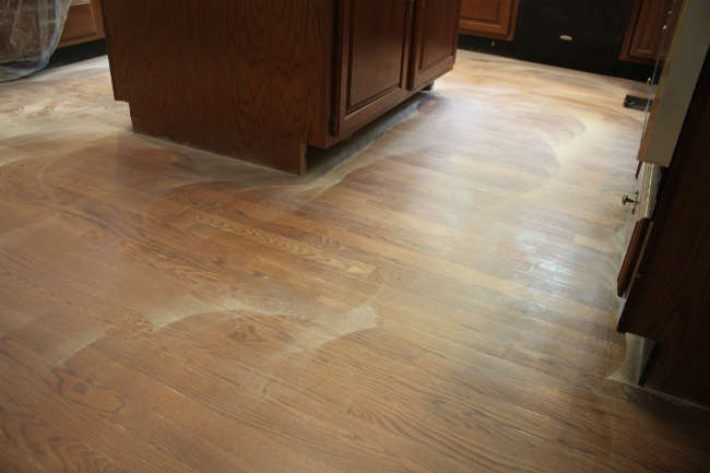 """Refreshing"" the kitchen flooring with a fine grain sanding and a new topcoat of polyurethane."