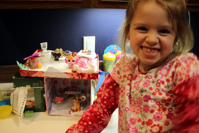 My daughter, the LPS enthusiast and one of many LPS creations she has made.  Using shoeboxes and paper, she made everything from a house with a swing, a shower and even a computer!