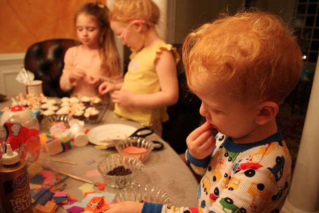 The girls worked hard on the decorating while their brother worked hard on tasting all of the candy toppings.