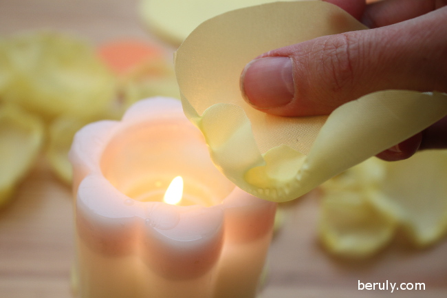 Burning the edges of the circles with a candle to make them curl and seal the ends.